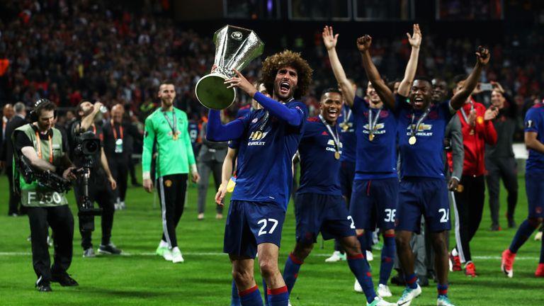 Fellaini holds up the Europa League trophy