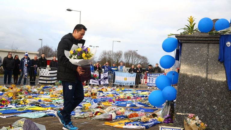 Cardiff CEO Ken Chu puts flowers at Cardiff Stadium on Friday