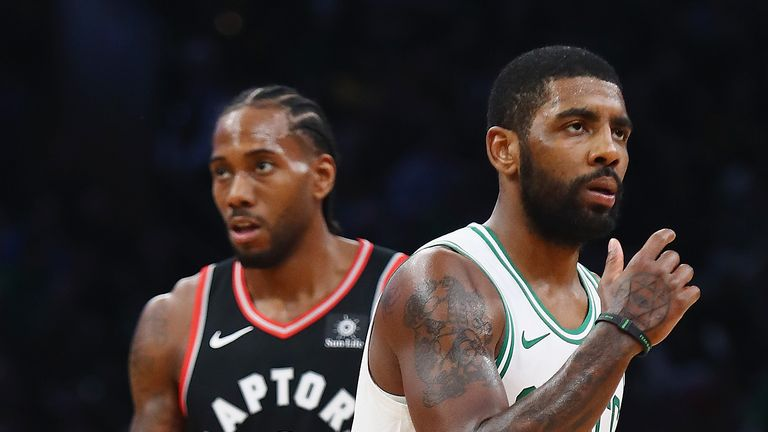 Kawhi Leonard #2 of the Toronto Raptors and Kyrie Irving #11 of the Boston Celtics look on during the first half at TD Garden on November 16, 2018 in Boston, Massachusetts.