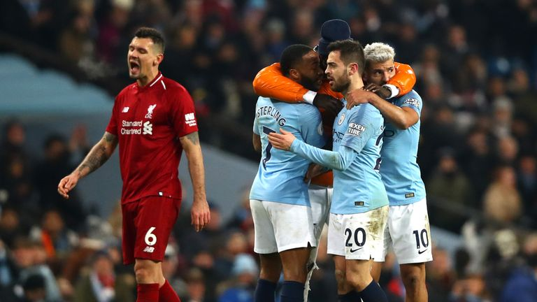 Manchester City celebrate victory on a difficult night for Dejan Lovren of Liverpool