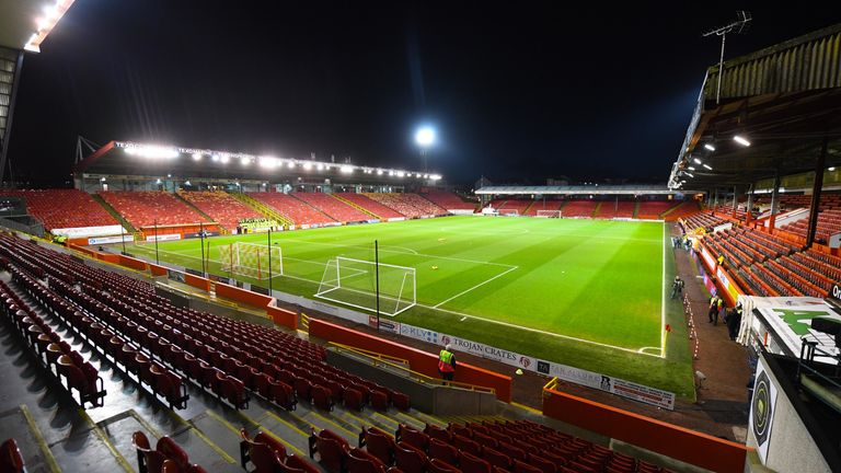 Two fans have been charged over allegations of racism at Pittodrie