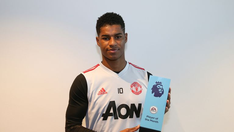 Marcus Rashford poses with his EA Sports Player of the Month award at the Aon Training Complex