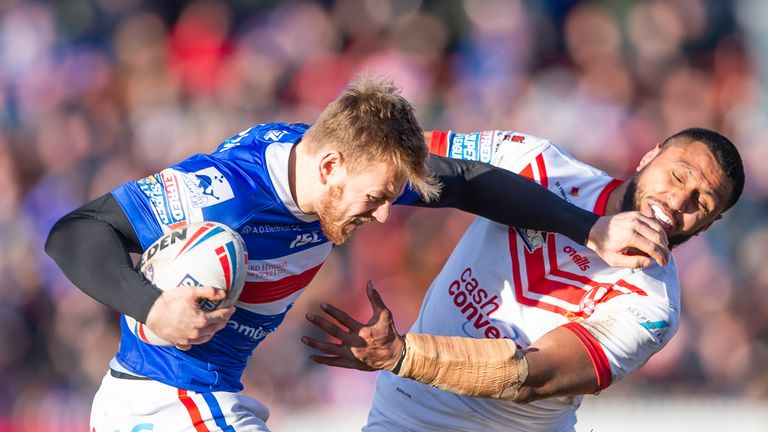 Wakefield's Tom Johnstone fends off St Helens' Dominique Peyroux