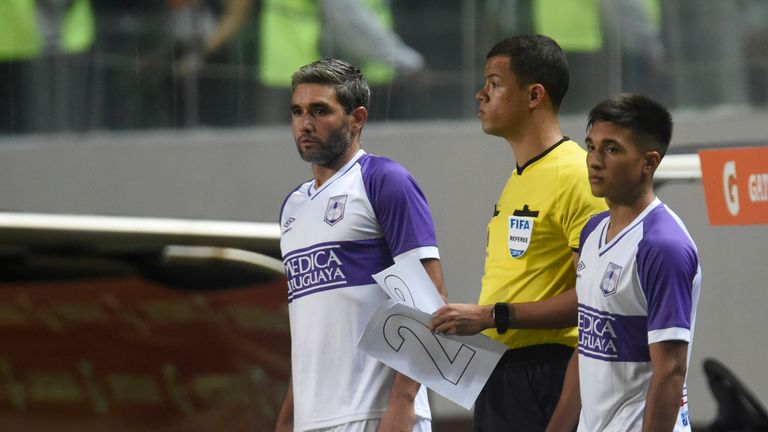 Defensor Sporting prepare their substitutions as the fourth official holds the paper numbers