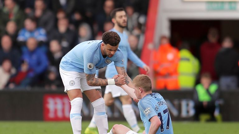 Kevin De Bruyne is helped up by Kyle Walker after going down injured