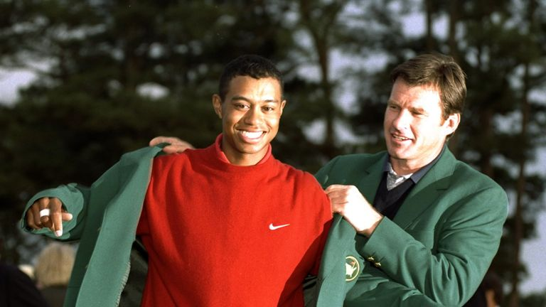 Nick Faldo helps Woods into his first green jacket in 1997