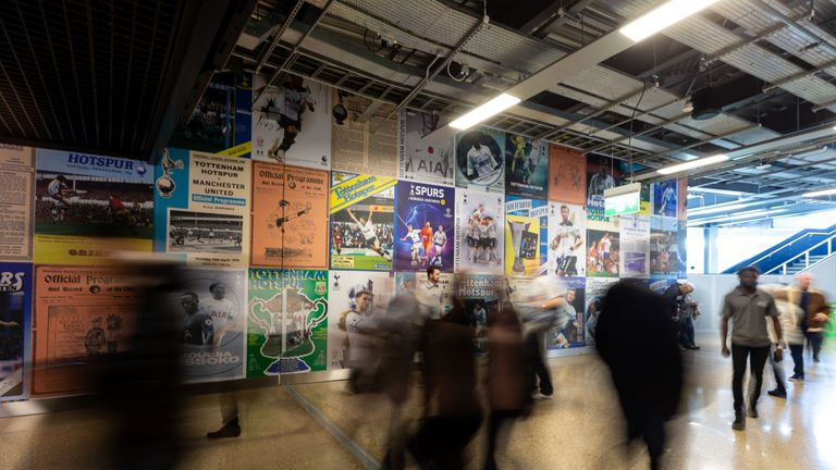 Supporters walk by a wall covered in large, poster-sized imagery of match day programmes at Tottenham Hotspurs' new stadium