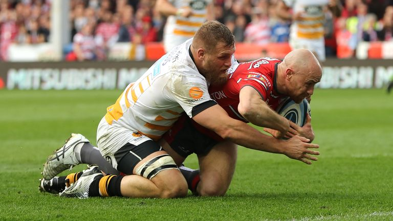Willi Heinz scores a try for Gloucester despite the attentions of Brad Shields