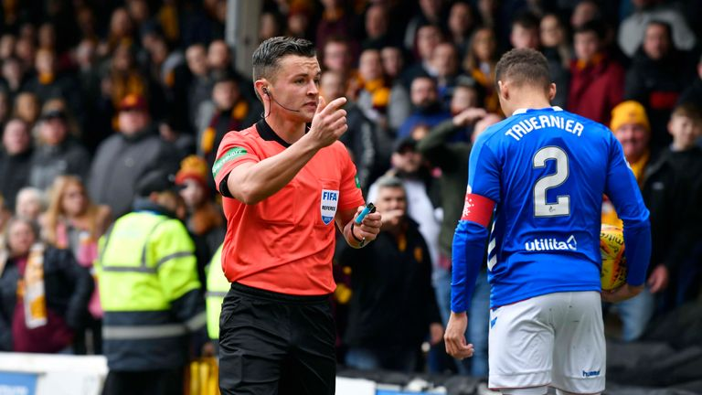 Nick Walsh holds a lighter during a first-half incident involving James Tavernier