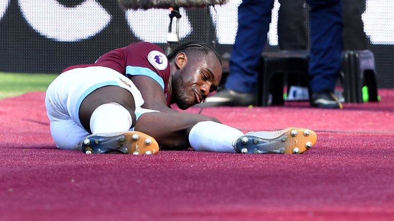 Michail Antonio celebrates his goal by stroking West Ham's new claret pitchside carpet