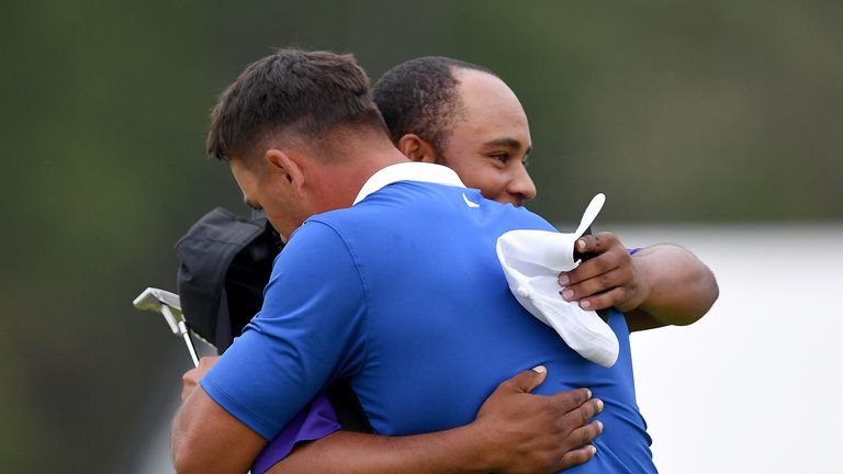 Harold Varner III hugs Brooks Koepka after they completed their final rounds at the PGA Championship