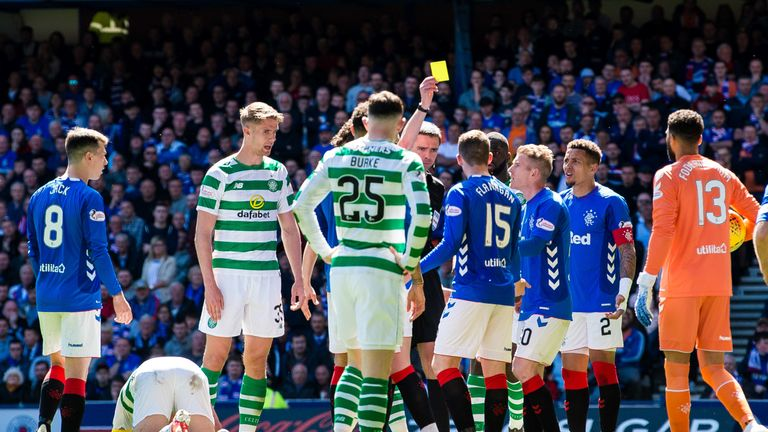 Referee Kevin Clancy books Rangers' Jon Flanagan (right) after a clash with Celtic's Scott Brown