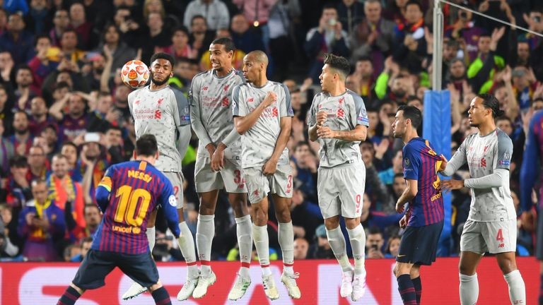 Liverpool players look on as Barcelona's Lionel Messi scores a wonderful free-kick at the Nou Camp