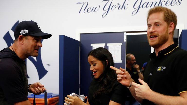 New York Yankees manager Aaron Boone presents the royal couple with a gift for their son Archie