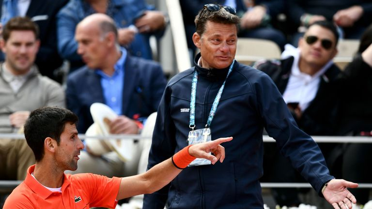 Djokovic speaks with a tournament supervisor about the windy conditions, prior to the match being briefly suspended in the second set for rain