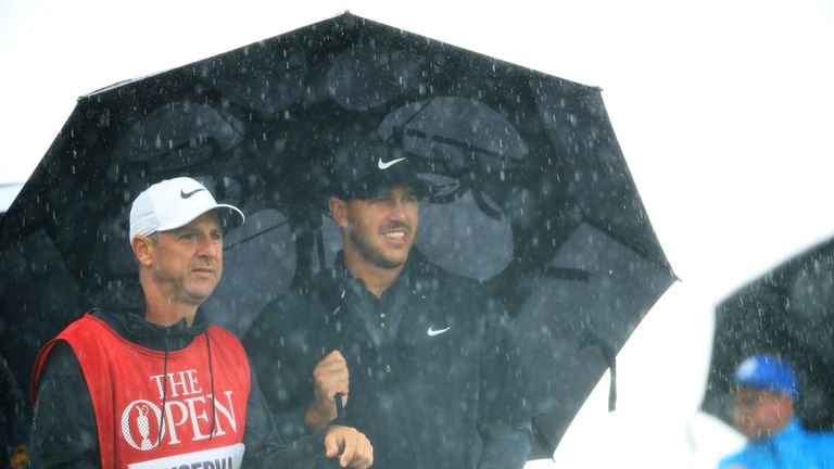 Koepka shelters from the rain with his caddie Ricky Elliott