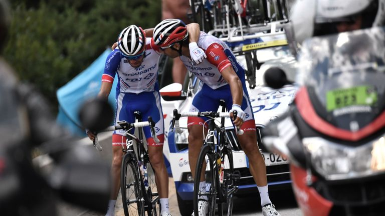 France's Thibaut Pinot (L) is comforted by a team-mate as he is forced to quit the Tour