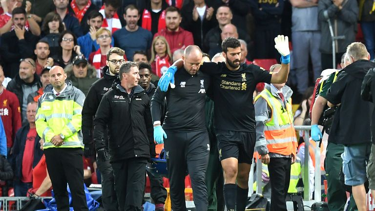 Alisson leaves the pitch following an off-the-ball injury