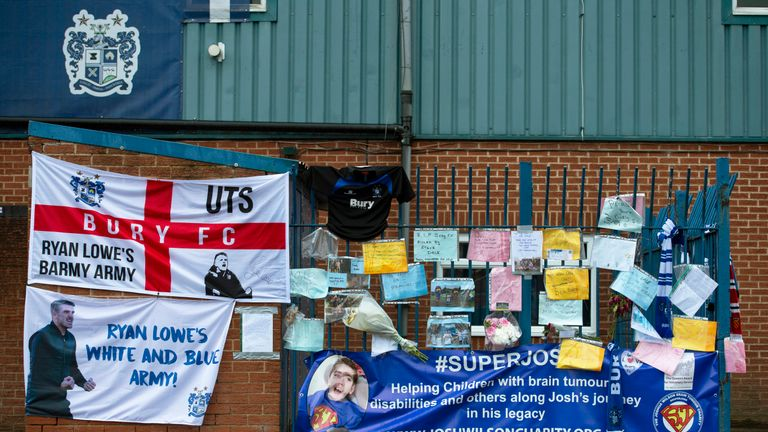 Banners and messages of support are left outside Bury's Gigg Lane