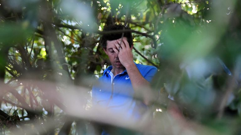 Rory McIlroy shows the strain after finding his ball in the shrubbery on the 18th