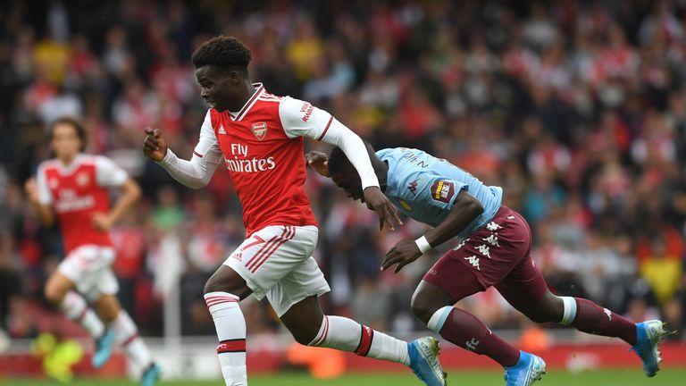 Saka sprints past an Aston Villa defender at the Emirates Stadium