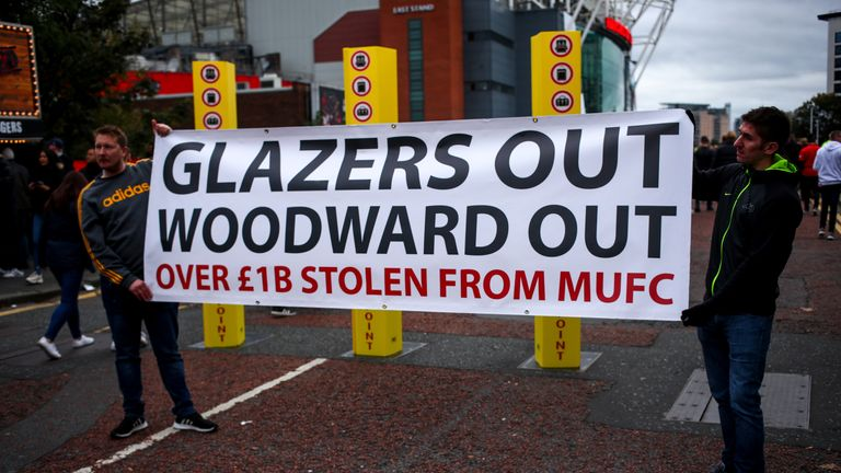 Fans hold an anti-Woodward and anti-Glazer banner before a home game in October