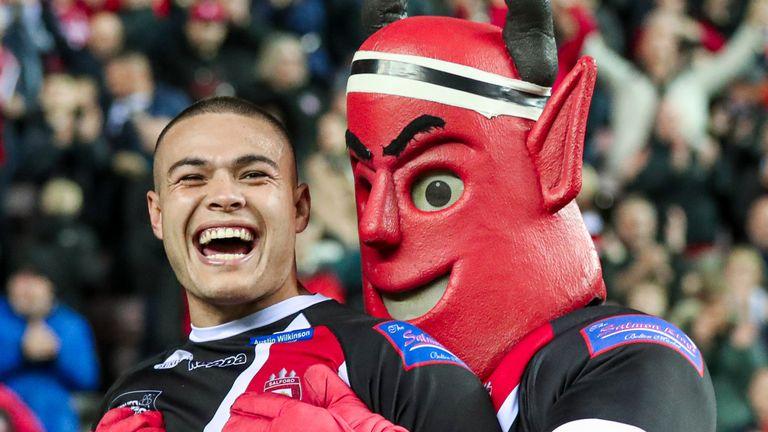 Salford's Tui Lolohea and the mascot celebrate the semi-final victory over Wigan Warriors