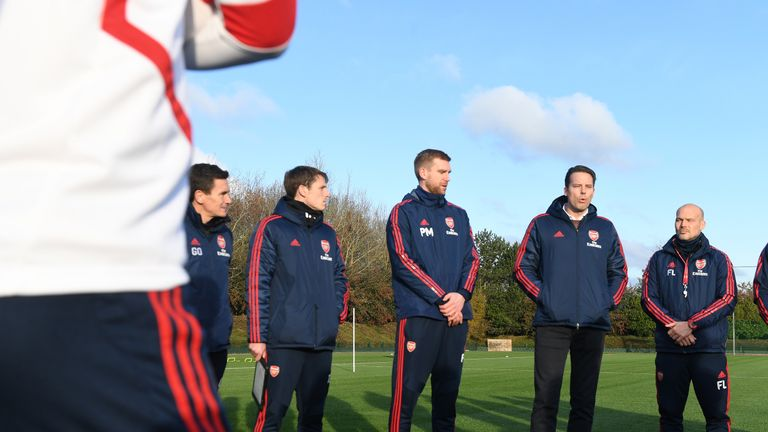 Josh Kroenke (second right) speaks with Arsenal players and coaching staff on Saturday during training