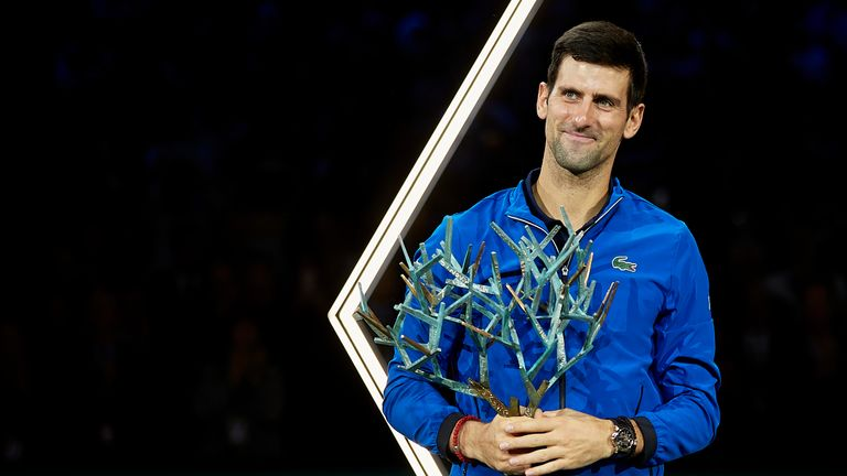 Djokovic celebrates with his trophy after winning the Paris Masters
