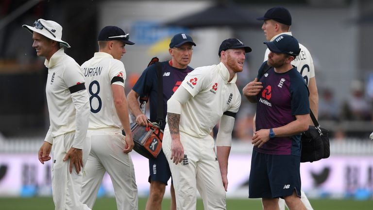 Ben Stokes holds his left knee in discomfort as he receives treatment from England's medical staff