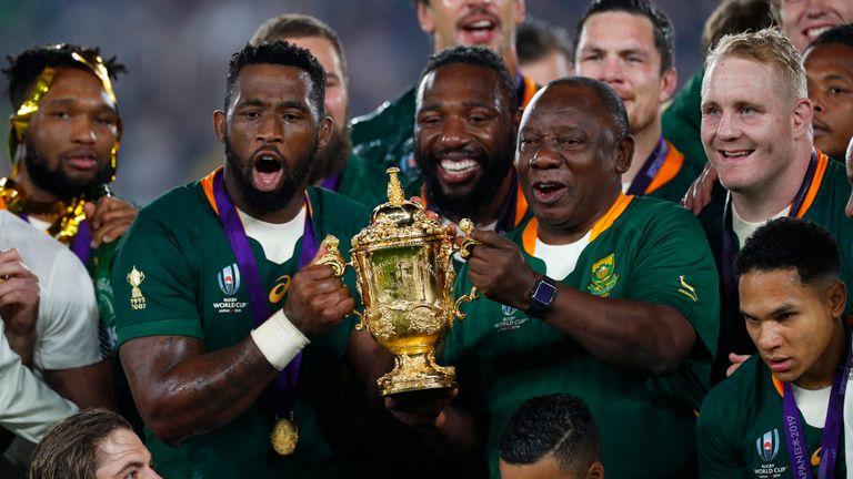 South Africa President Cyril Ramaphosa, right, lifts the Web Ellis Cup with Siya Kolisi