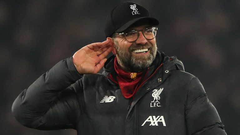 Jurgen Klopp cups his ear to the Anfield crowd after going 16 points clear in the Premier League