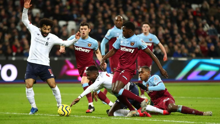 Divock Origi goes down inside the box under a challenge from Issa Diop