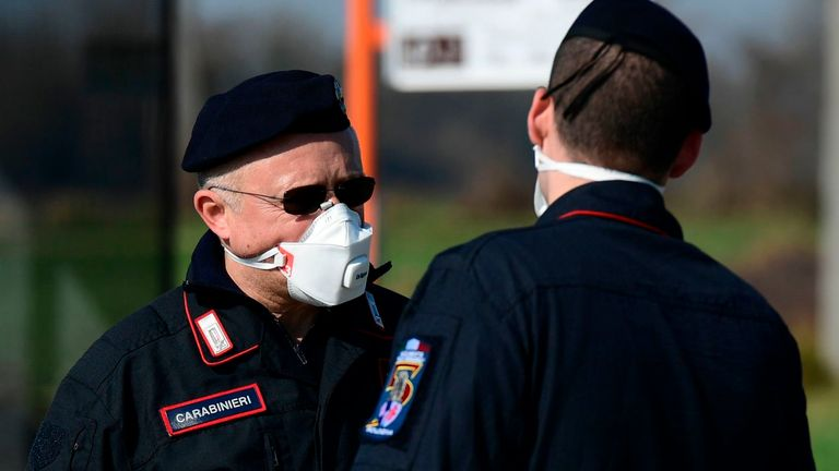 Italian police officers wear respiratory masks at a checkpoint amid the country's coronavirus outbreak