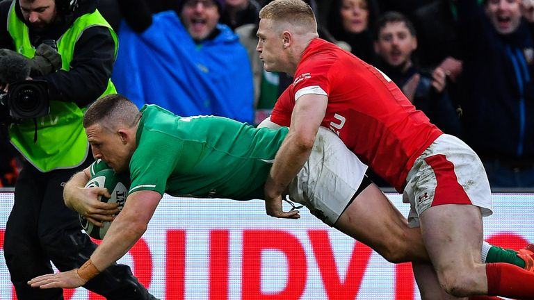 Andrew Conway dives over to score Ireland's bonus-point try despite the efforts of Johnny McNicholl