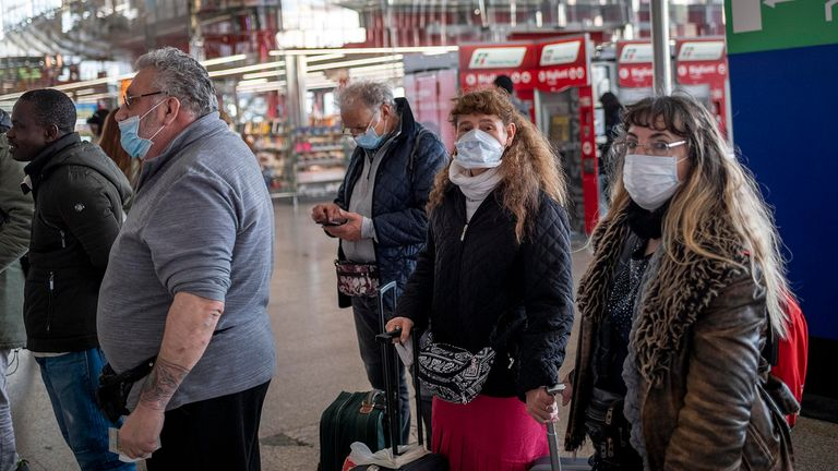 People wear face masks wait at the Termini Central Station in Rome