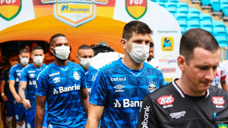 Gremio players walk out of tunnel for their match against Sao Luiz wearing face masks