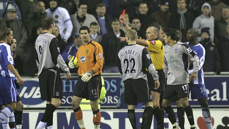 Mike Dean brandishes the red card at Ferguson following a penalty-box melee