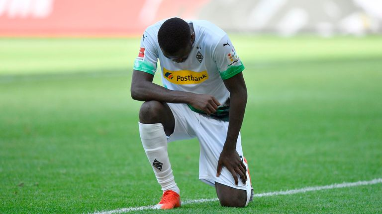Marcus Thuram kneels after scoring for Borussia Monchengladbach against Union Berlin