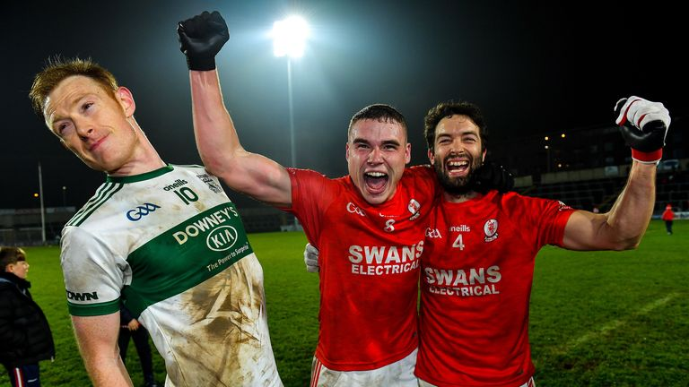 Éire Óg players Jordan Morrissey and Brendan Kavanagh celebrate their Leinster Club Championship victory, as Brian Glynn of Portlaoise attempts to make his way out of the shot