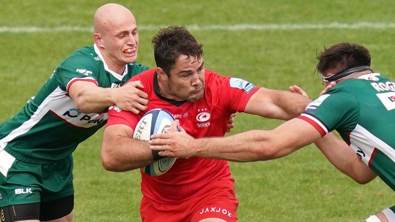 Brad Barritt is tackled by London Irish's Matt Rogerson (R) and Jacob Atkins