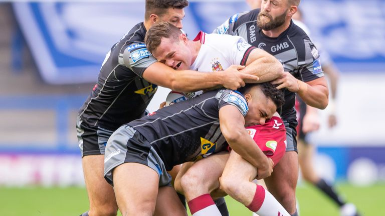 Wigan's Joe Burgess is tackled by Castleford's Alex Foster, Derrel Olpherts and Paul McShane