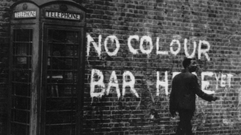 circa 1959: A black man walking down a Notting Hill Street. The graffiti behind him reads, 'No Colour Bar Here - Yet'