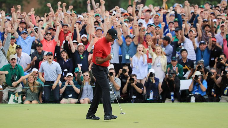 Woods celebrates his victory on the 18th green amid raucous celebrations from the patrons