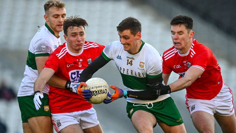 Sweeney is tackled by Sean Meehan and Maurice Shanley of Cork
