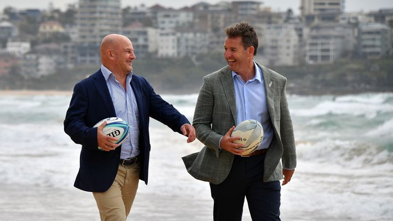 Rugby Australia interim chief executive Rob Clarke (L) and New Zealand Rugby chief executive Mark Robinson walk on Manly Beach after a press conference in Sydney