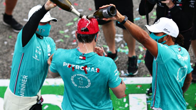 Lewis Hamilton and Valtteri Bottas pour champagne over Toto Wolff after Mercedes' won their seventh Constructors' Championship