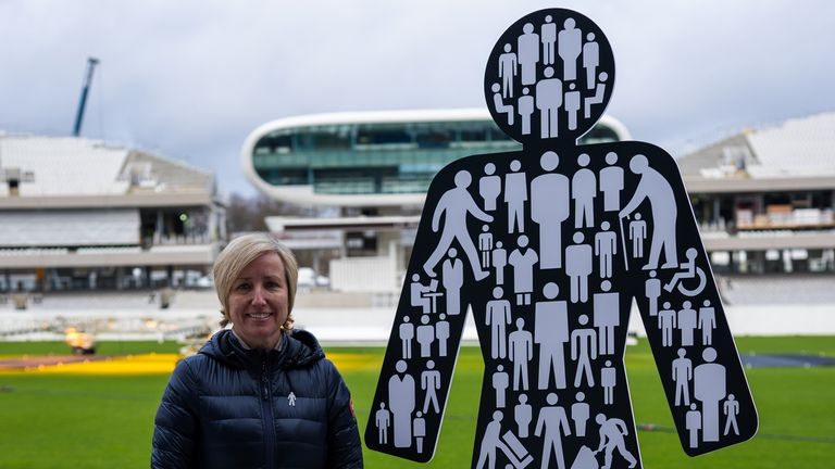 Lauren Clarke, wife of Bob Willis, stands next to the Prostate Cancer UK logo