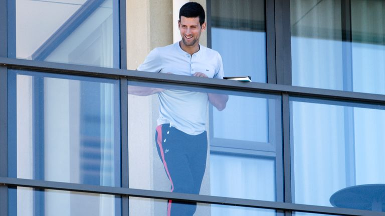 Djokovic stands on the balcony at his accommodation in Adelaide