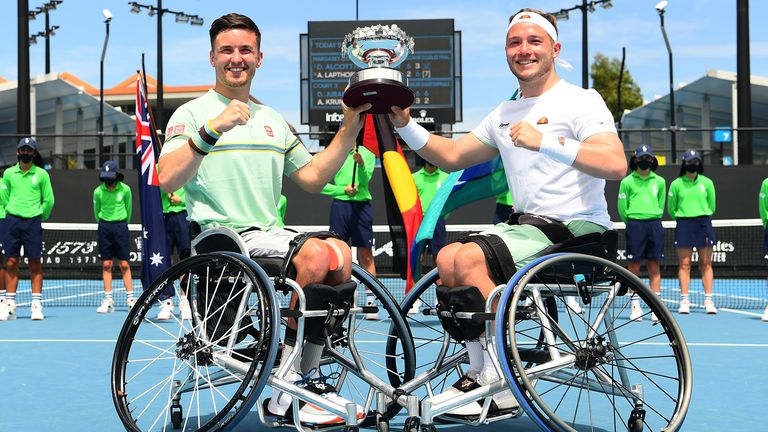 Reid and Hewett pose with the championship trophy after winning the men's wheelchair doubles title